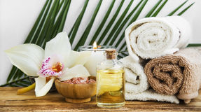 Spa orchid setting with towels, body oil, candle and salt Royalty Free Stock Photos