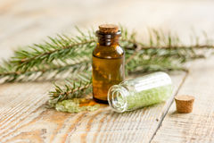 Spa with organic spruce oil and sea salt in glass bottles on wooden table background Royalty Free Stock Images