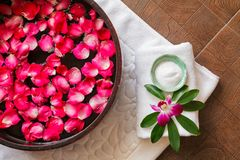 Spa pedicure treatment with foot bath in bowl, red rose petals ,orchid,foot scrub , Royalty Free Stock Photography