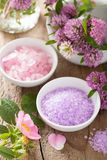 Spa with pink herbal salt and wild rose flowers clover Stock Photos