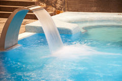 Spa pool in action. Empty Swimming pool with waterfall jet,  and jacuzzi in action Stock Photography