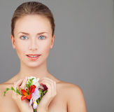 Spa Portrait of Perfect Woman with Beautiful Face. Natural Makeup and Bright Colorful Flowers on Gray Background Royalty Free Stock Photo