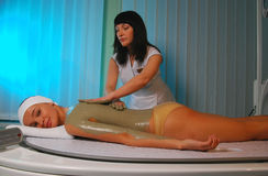 Spa procedure. A sea mud full body wrap being applied to the body at a luxury spa Royalty Free Stock Photo