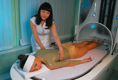 Spa procedure. A sea mud full body wrap being applied to the body at a luxury spa Royalty Free Stock Photography