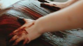 SPA- procedure De masseur maakt chocolade die jonge vrouw verpakken stock videobeelden