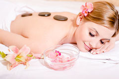 During spa procedures stone therapy massage blond pretty girl having fun eyes closed picture Royalty Free Stock Images