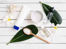 Spa products, aromatherapy oil and salt with Plumeria flower. Spa products, aromatherapy oil and salt with Plumeria flower and leaf flat lay  on wooden table Royalty Free Stock Photos