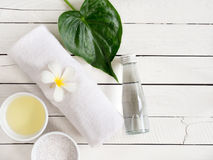 Spa products, aromatherapy oil, salt and white towel with copy s. Spa products, aromatherapy oil , salt and white towel with Plumeria flower and leaf  on wooden Royalty Free Stock Photos