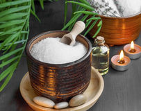 Spa products with bath salt, bath oil, massage stones and candle Royalty Free Stock Images