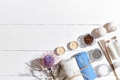 Spa products. Bath salts, dry flowers lavender, soap, candles and towel. Flat lay on white wooden background, top view. Stock Photos