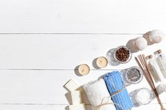Spa products. Bath salts, dry flowers lavender, soap, candles and towel. Flat lay on white wooden background, top view. Royalty Free Stock Image