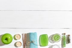 Spa products. Bath salts, soap, candles and towel. Flat lay on white wooden background, top view. Royalty Free Stock Image