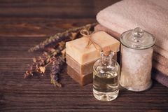 Spa products for facial and body care. Natural  sea salt, homemade soap, massage oil and colorful towels. Spa and bodycare concept Stock Image