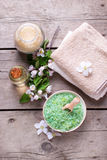 Spa products. Sea salt in bowl, towels, aroma oil in bottle and flowers on vintage wooden background. Selective focus stock photo