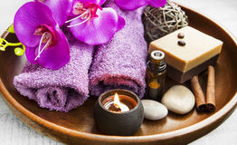 Spa products in wooden tray with burning candles and orchid flow Royalty Free Stock Photos
