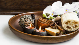 Spa products in wooden tray with burning candles and orchid flow Royalty Free Stock Photo