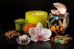 Spa produkter och den vita orkidén blommar och stearinljus på svart backgr Arkivbilder