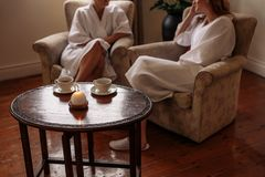 Spa reception area with women waiting in background. Spa reception area with women sitting in background waiting. Focus on table with candle and coffee cups stock photos