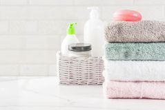 Stack clean bath towels. Spa relax and bath concept, sea salt, soap, with cosmetics and towels in bathroom white background, copy space top view Stock Photos