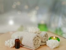 Spa aromatherapy concept. Towel, essential oil, handmade flower soap, burning candle in green glass on wooden table stock photo