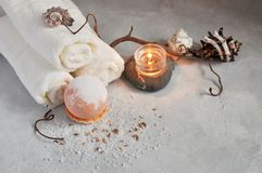 Spa relax concept. White Terry towels, stones, a candle and a bomb for a bath of sea salt on a gray textured background. royalty free stock photography