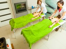 Massage with hot rocks stones in beautician Royalty Free Stock Photos