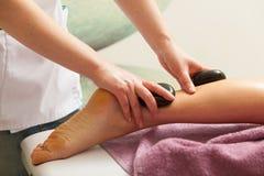 Masseuse doing legs massage with hot stones Stock Photos