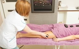 Masseuse doing legs massage with hot stones. Spa relaxation, healthy pleasure concept. Woman lying on stomach, female masseuse doing legs and feet massage with Royalty Free Stock Photos