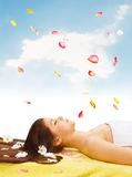Spa Relaxing. Portrait of  Beautiful brunette woman laying on towel around  flowers Royalty Free Stock Image