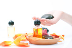 Spa relaxing. Scene with rock in the hand, perfumed oil and petals Stock Image