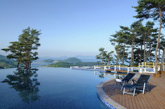 Spa resort hotel infinity swimming pool, mountains and islands in distance Stock Photo