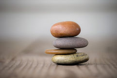 Spa rocks in a stack on wood surface Royalty Free Stock Photography