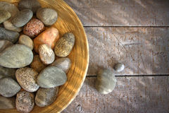 Spa rocks in wooden bowl on rustic wood Royalty Free Stock Photography