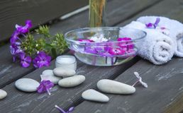 spa round sea pebbles and pink flowers on wooden background royalty free stock photo