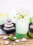 Spa salon. Photo of beautiful spa still life, spa stones, candle, white lily flower on bamboo table in spa-salon, aroma therapy, zen balance, bath items, beauty Royalty Free Stock Images