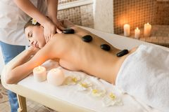 Spa salon. Attractive woman relaxing and having stone therapy in spa salon royalty free stock photography
