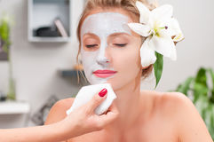 Spa salon. Beautiful woman with clay facial mask at beauty salon Royalty Free Stock Image