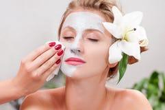 Spa salon. Beautiful woman with clay facial mask at beauty salon Stock Photo