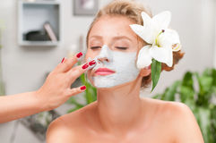 Spa salon. Beautiful woman with clay facial mask at beauty salon Royalty Free Stock Photos