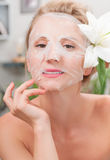 Spa salon. Beautiful woman with facial mask at beauty salon Stock Photo