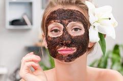 Spa salon. Beautiful woman with facial mask at beauty salon Royalty Free Stock Photography