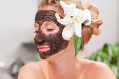 Spa salon. Beautiful woman with facial mask at beauty salon stock photos