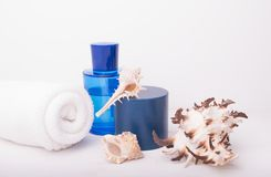 Spa salon concept with rolled white towel, blue bottle and seashells on white wooden background. Spa treatments. Spa background. S. Pace for a text stock photo