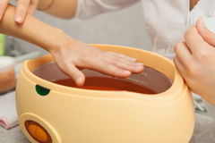 Spa salon. Manicure. Paraffin hand bath. Stock Photos