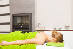 Spa salon. Woman relaxing having hot stone massage. Bodycare. Stock Photos