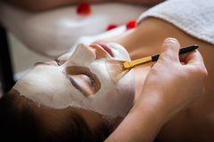 Spa salon. Young beautiful woman with facial mask, spa treatment stock image