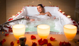 Spa salon. Young woman take bubble bath with candle royalty free stock photos
