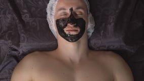 Spa salong Applicera en svart maskering till framsidan av en ung man lager videofilmer