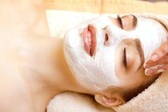 Spa salong: Härlig ung kvinna som har den ansikts- maskeringen royaltyfri foto