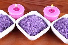 Spa salt. Lavender spa salt and lavender candles on a wooden background royalty free stock photo